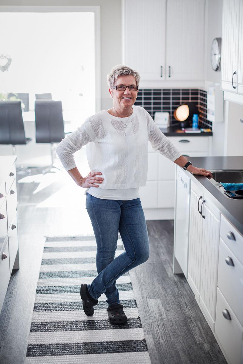 Kvinna står i sitt vita kök