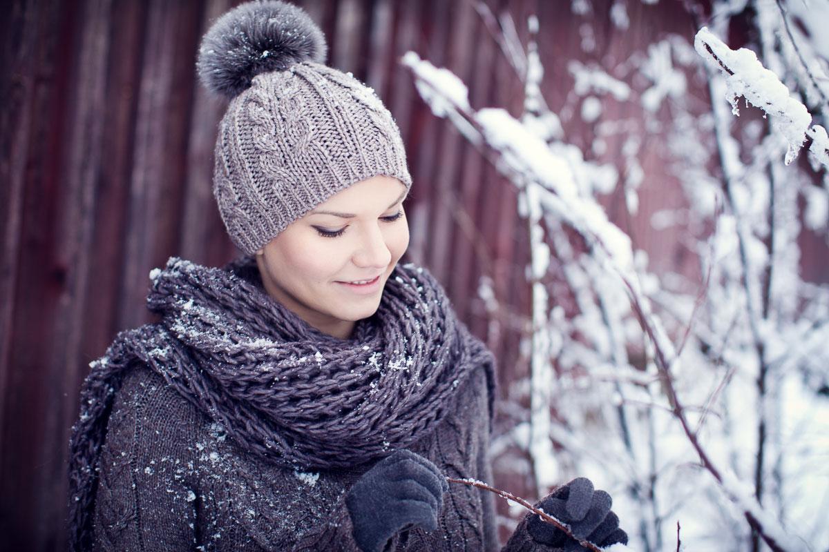 Kvinna i vinterlandskap och stickad tröja och mössa