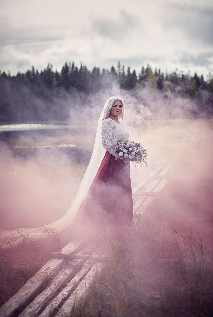brud står i en rosa dimma och tittar in i kameran