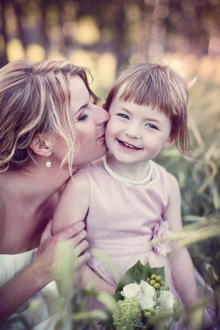 Mamma pussar sin dotter och brudnäbb på kinden