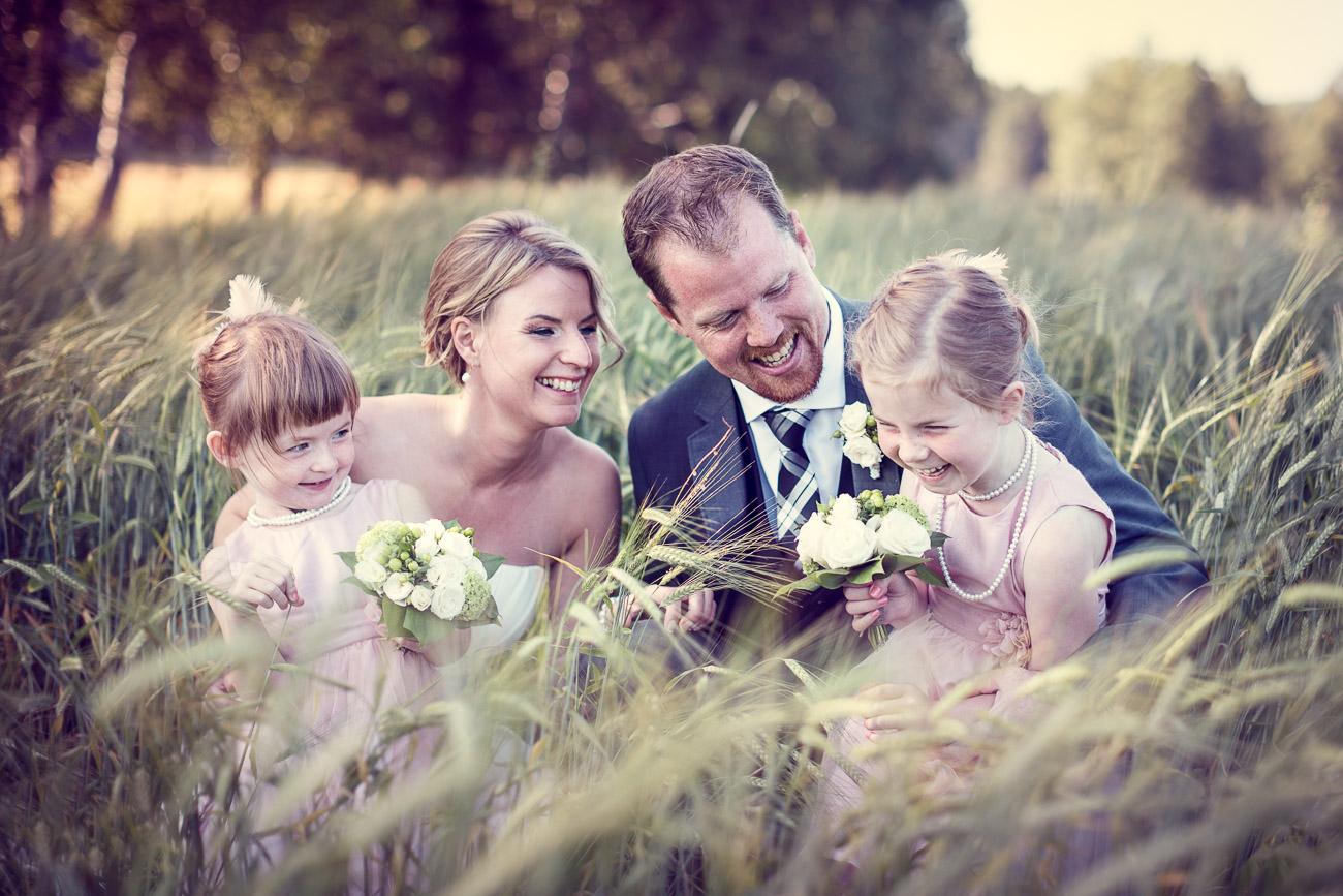 Familj sitter på en äng och skrattar