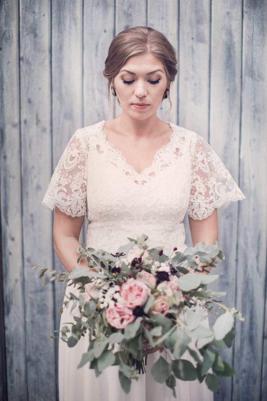 Brud håller i sin stora bröllopsbukett
