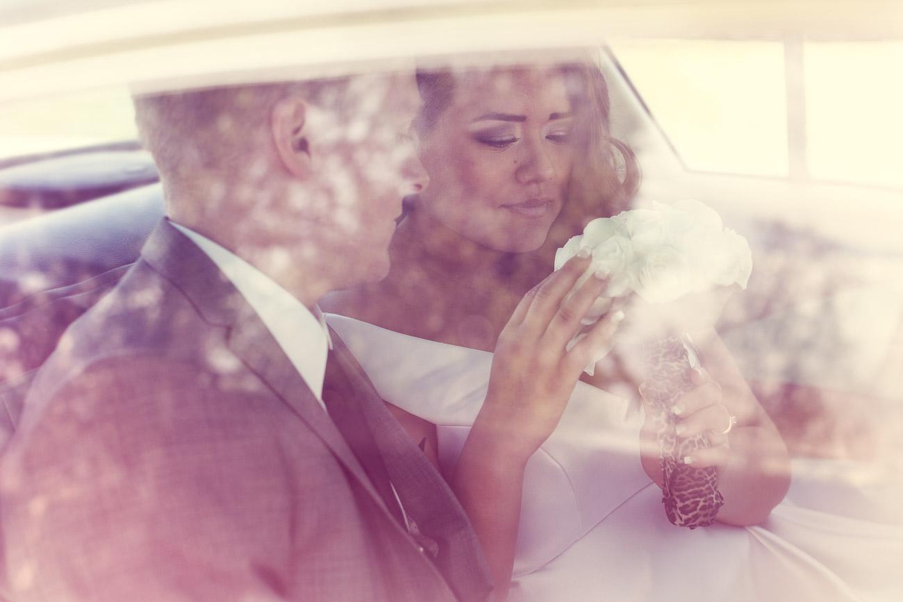 Brudpar sitter nära varandra i en bil