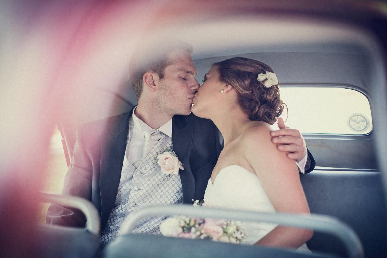 Brudpar pussas i en gammal bil