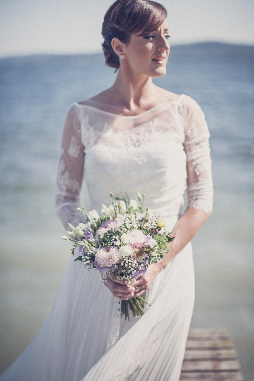 Brud på en brygga med sin bröllopsbukett