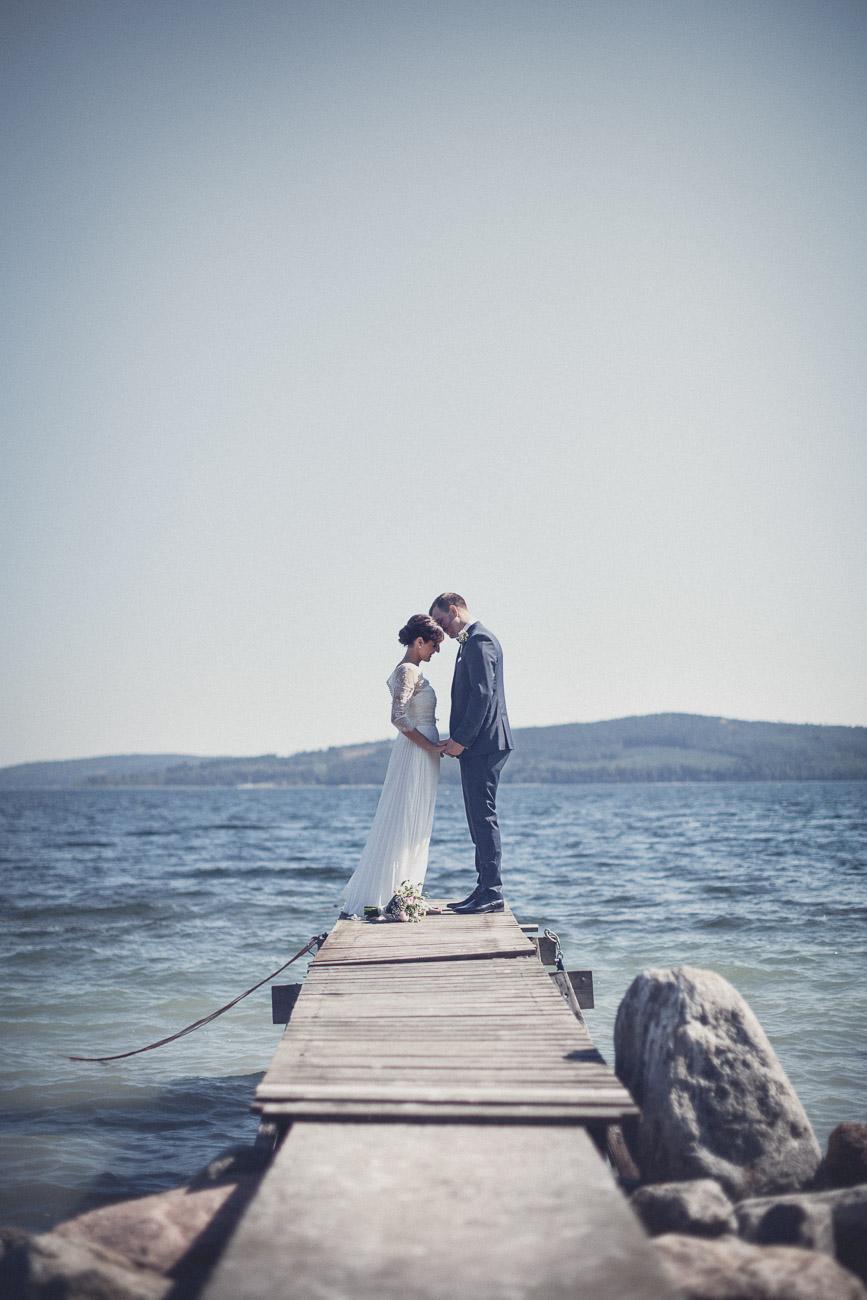 Brudpar står på en brygga vid havet