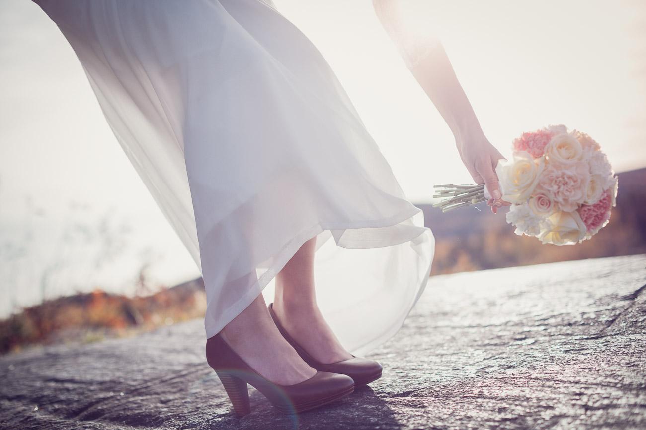 Brud lyfter upp sin bröllopsbukett