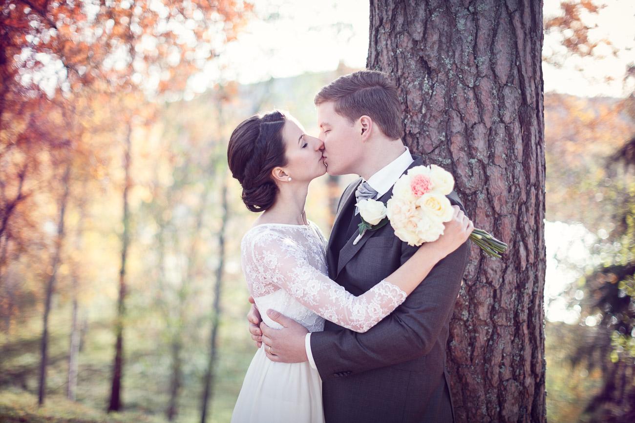 Brudpar pussas i ett höstlandskap