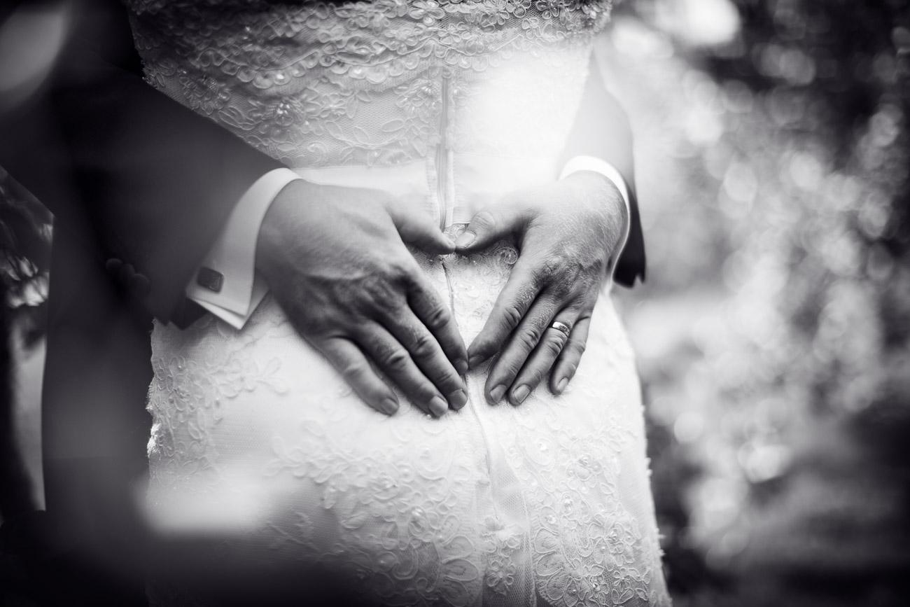 Brudpar kramas och bildar hjärta med händerna