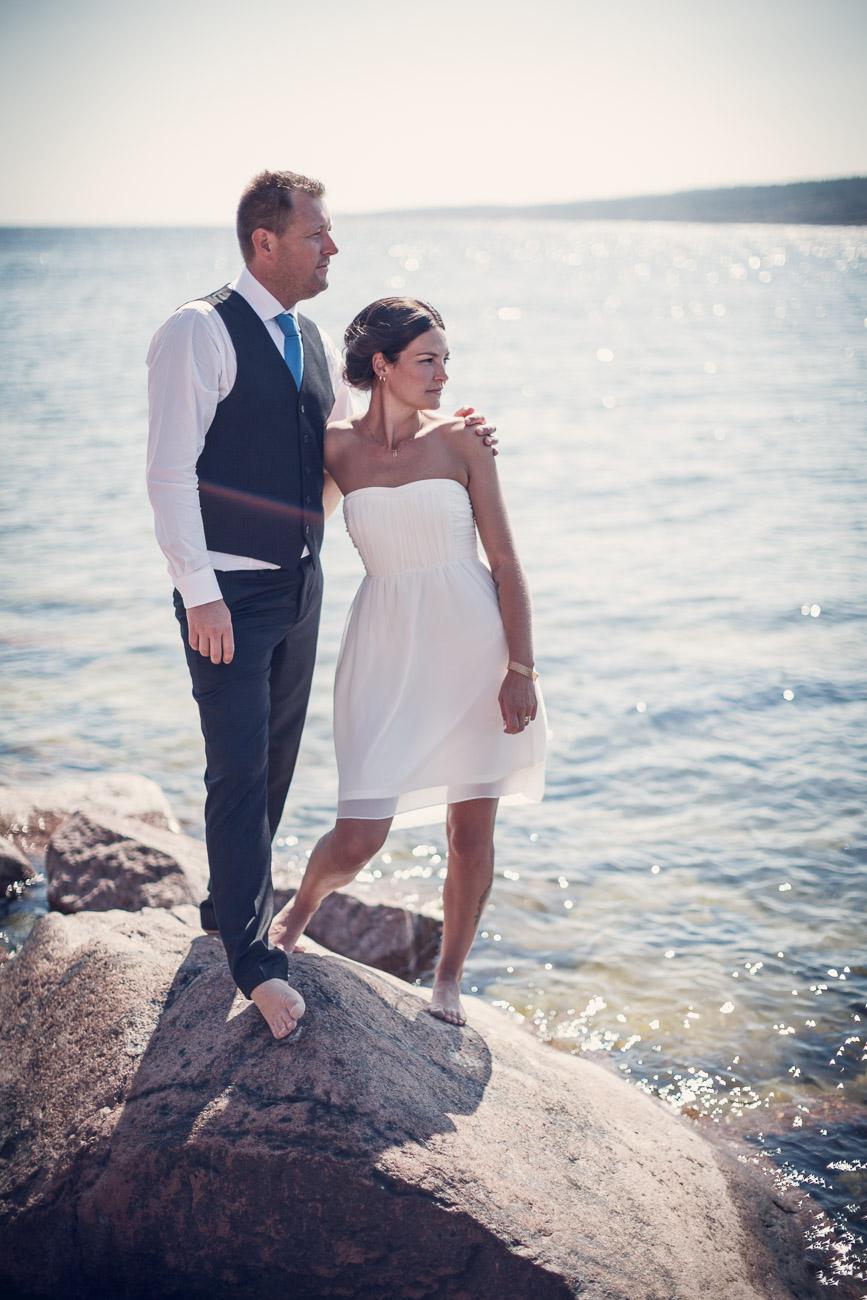 Brudpar håller om varandra och står på en klippa vid havet
