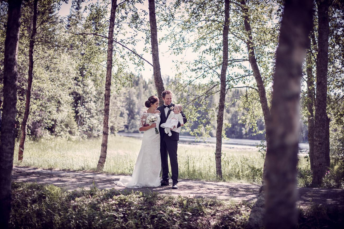 Blivande man och fru med sin bebis står bland träden