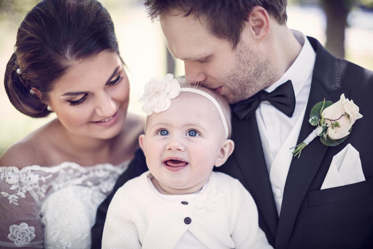 Blivande man och fru håller sitt lilla barn