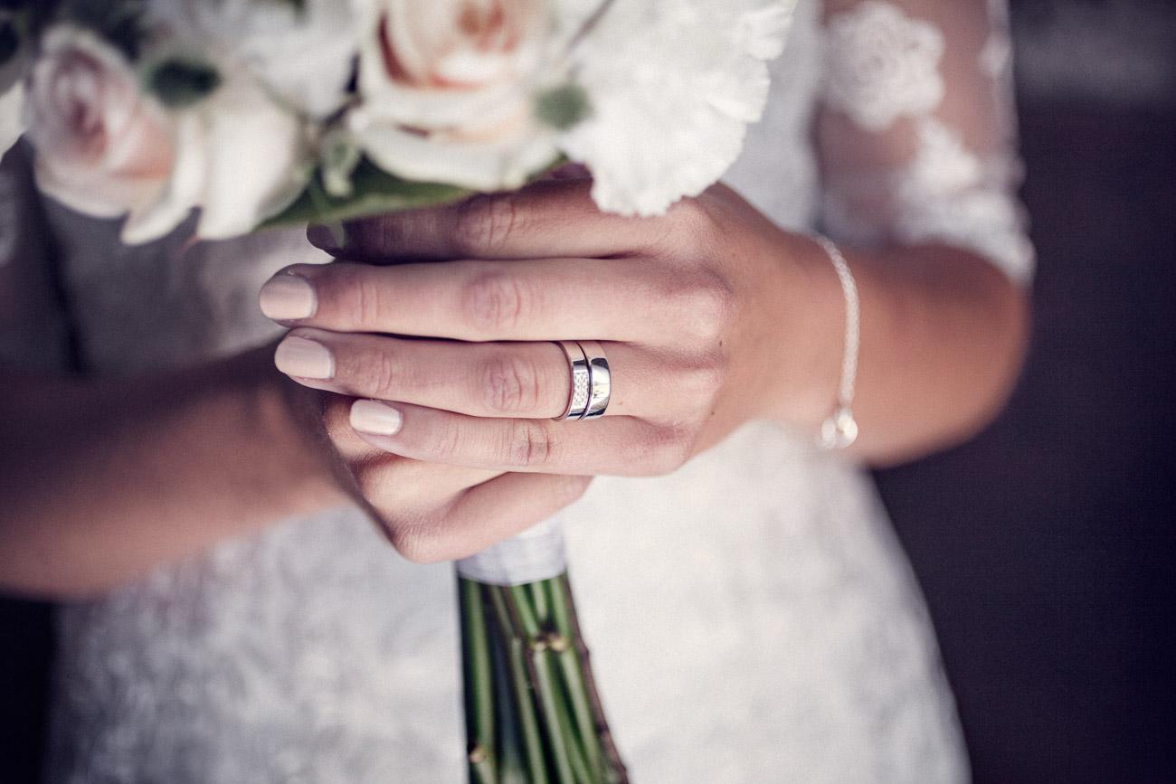 Vigselringen på fingret och håller en brudbukett