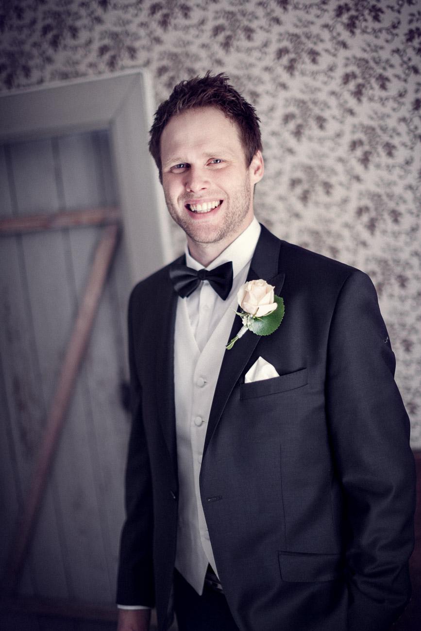 Brudgum i svart kostym i väntan på vigsel