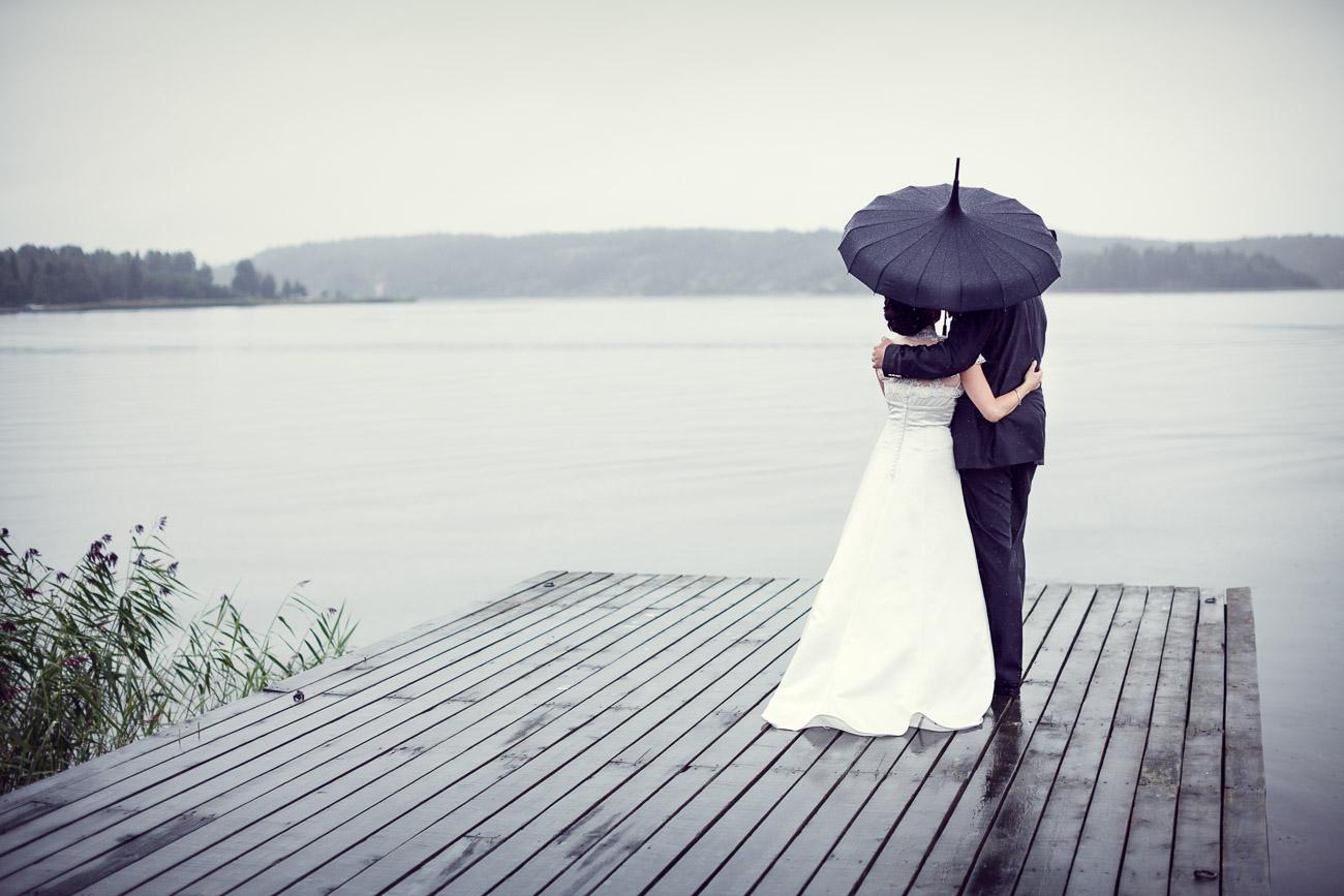 Brudpar håller om varandra under ett paraply på en brygga vid havet