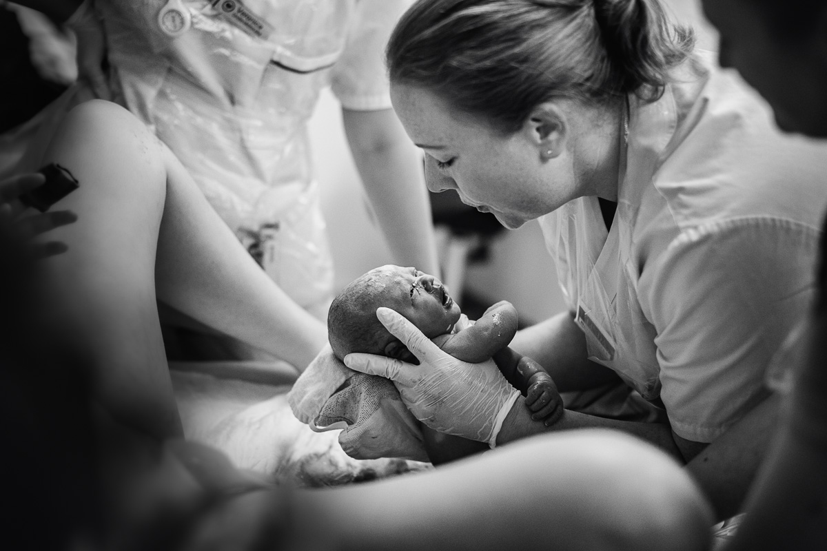 Nyfödd bebis plockas upp av barnmorskan