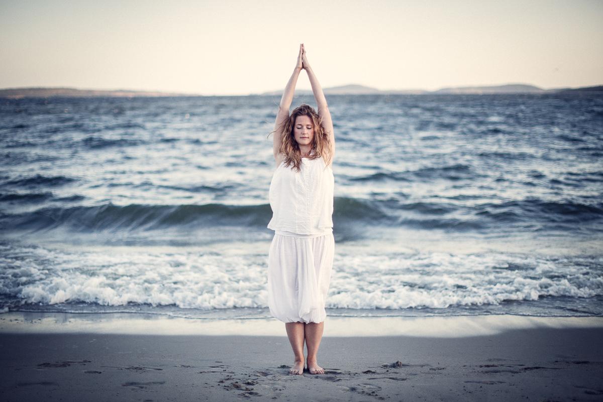 Tjej står i yogaställning på stranden i Örnsköldsvik