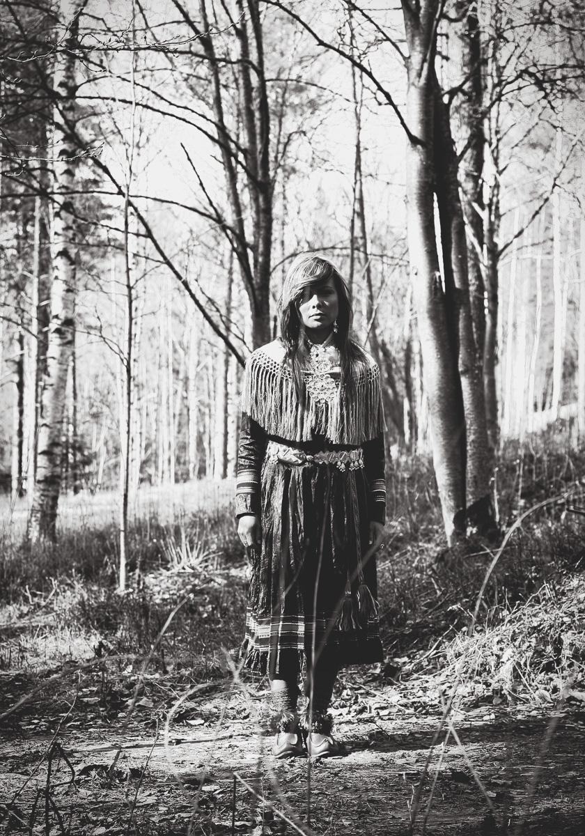 Samisk tjej står i en skog iklädd kolt