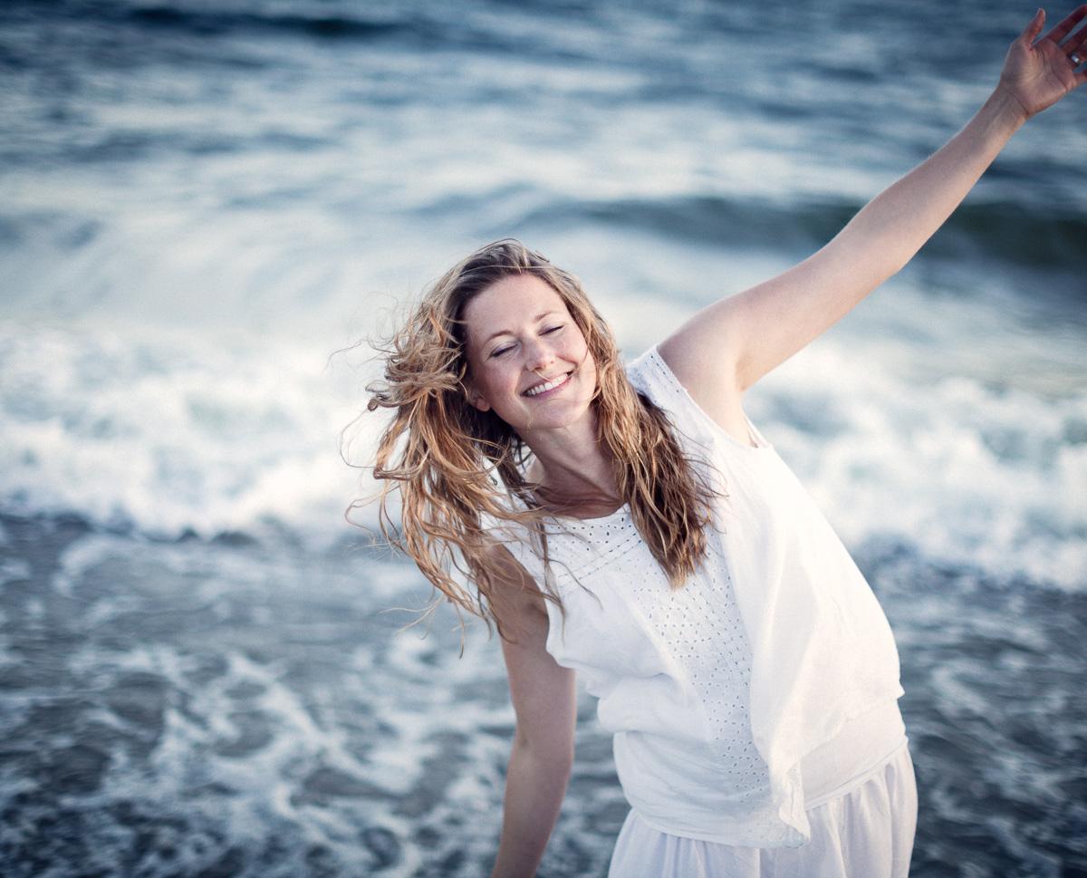 Glad yoga-tjej blundar på stranden i Örnsköldsvik
