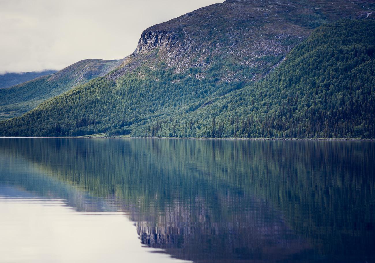 fjäll speglar sig i vattnet, det är sommar