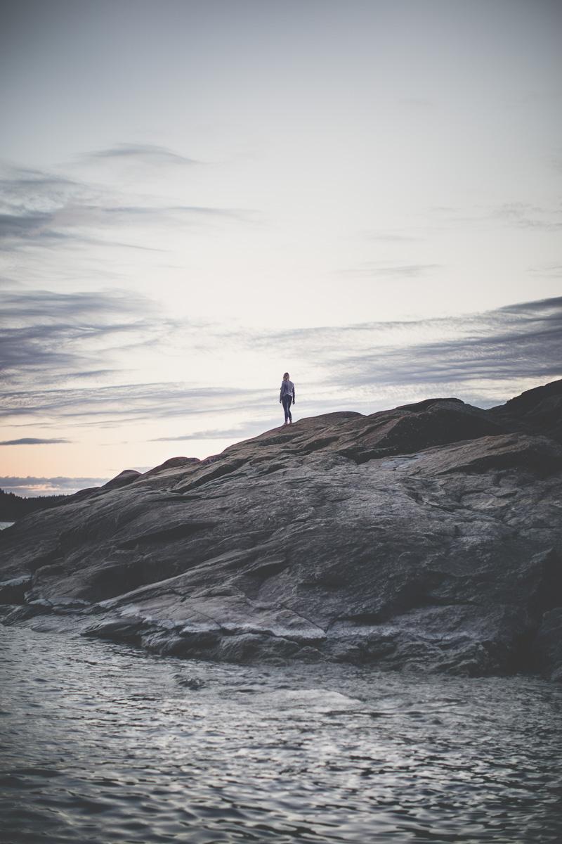 Kvinna står på en klippa vid havet i höga kusten