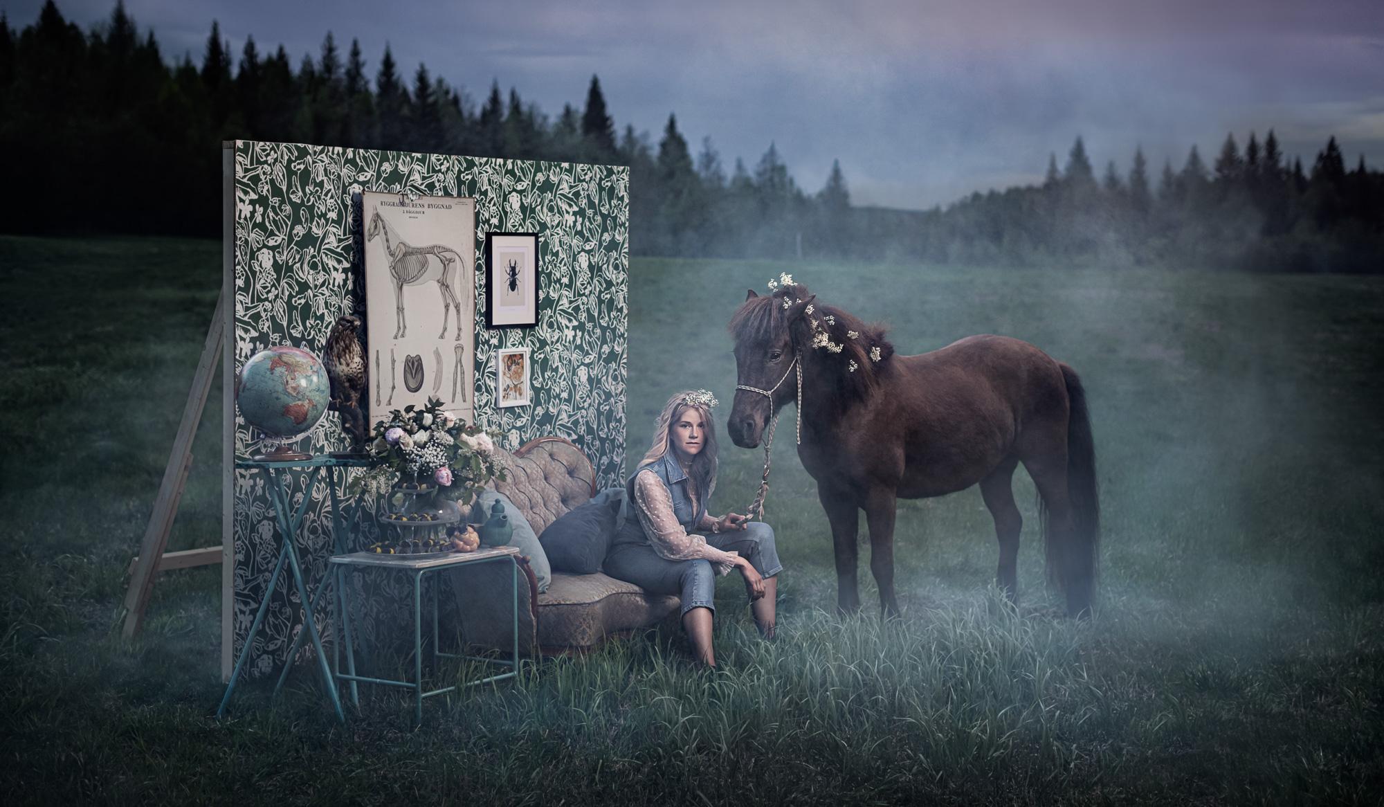 Flicka sitter i en soffa på en dimmig äng, en häst står bredvid