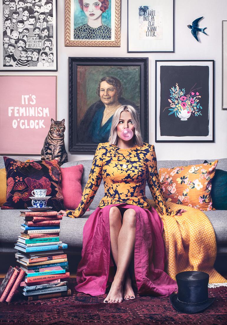 En färgstark bild av kvinna sitter i en soffa och blåser en bubbla med sitt tuggummi