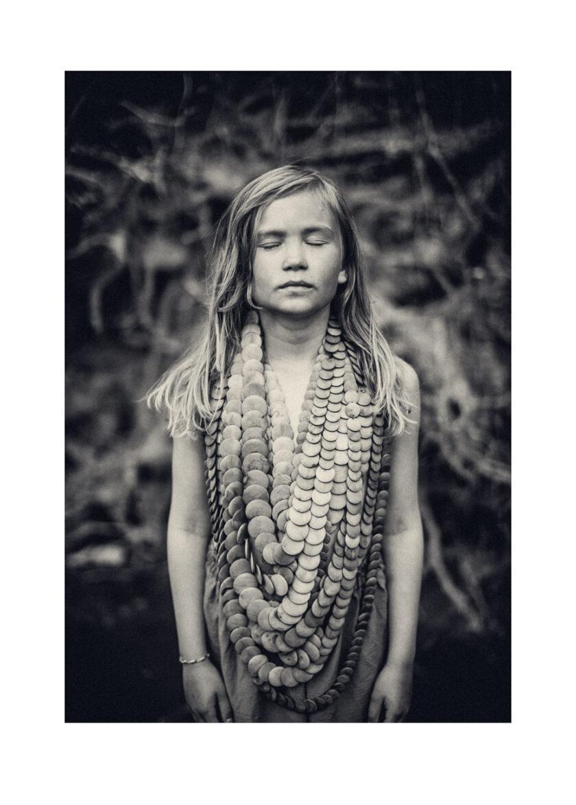 Flicka som blunda, bär ett stort halsband