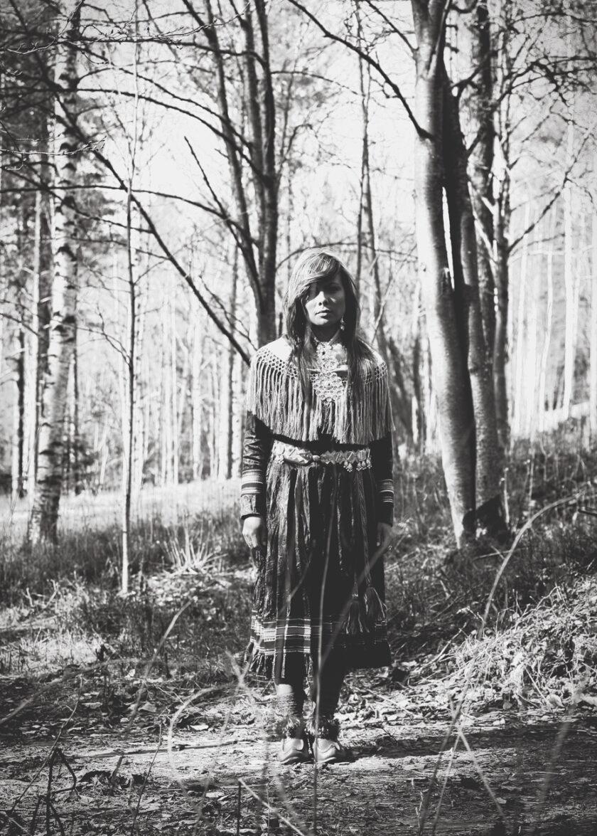 Samisk kvinna står i en enslig skog, hon backar sapmi
