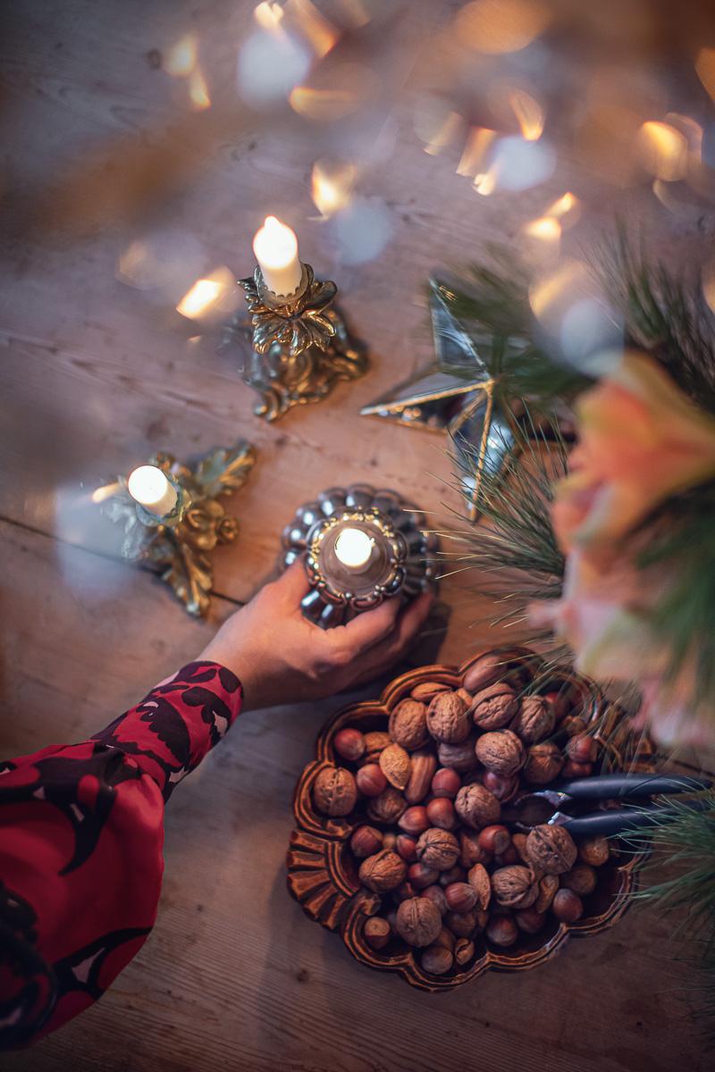 En kvinna flyttar på en fin julljusstake