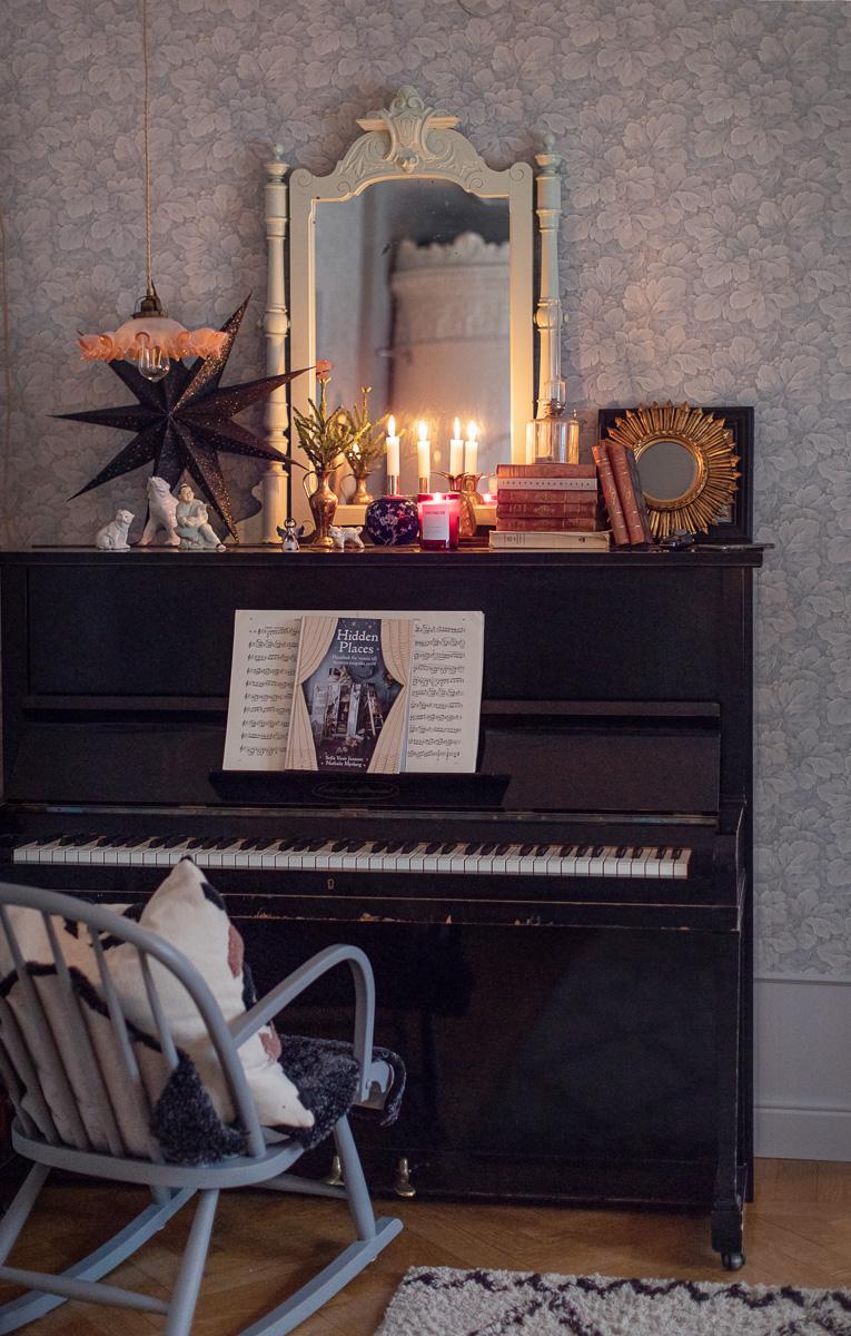 ett stort svart piano med tända ljus ovh julpynt
