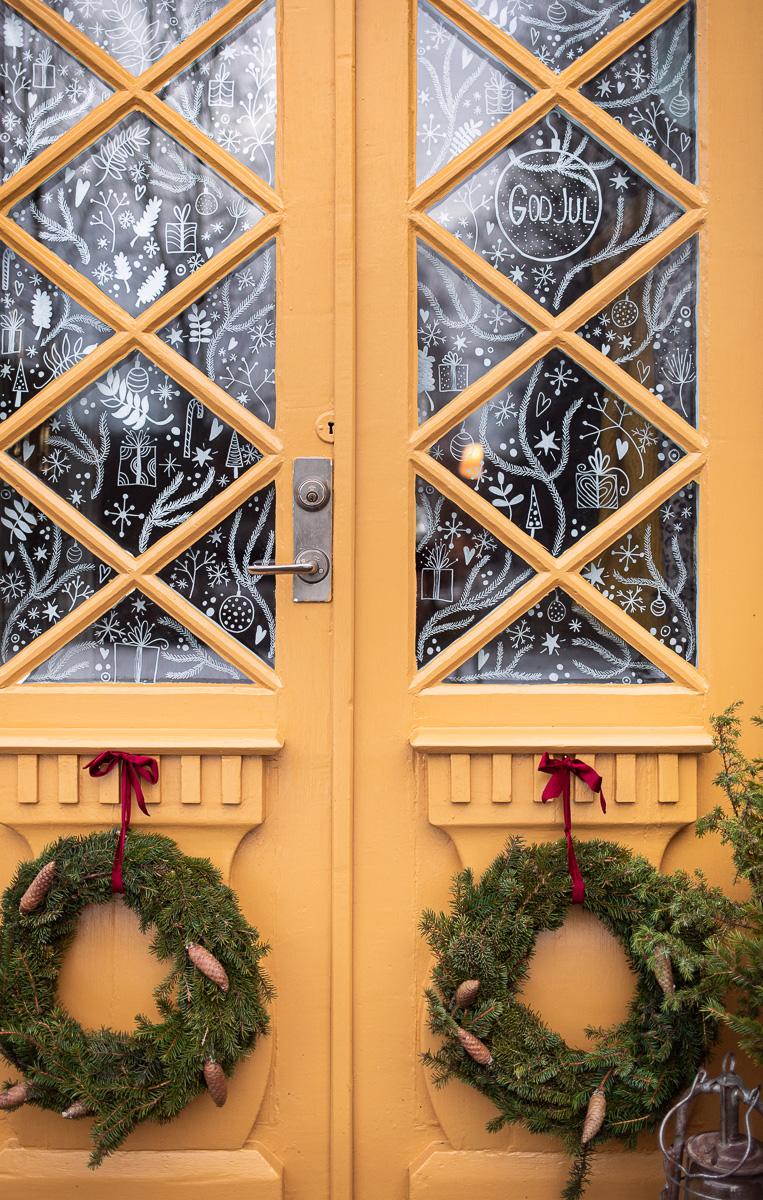 gula dubbeldörrar med två julkransar