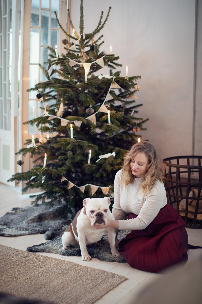 En hund och hennes matte sitter framför en julgran