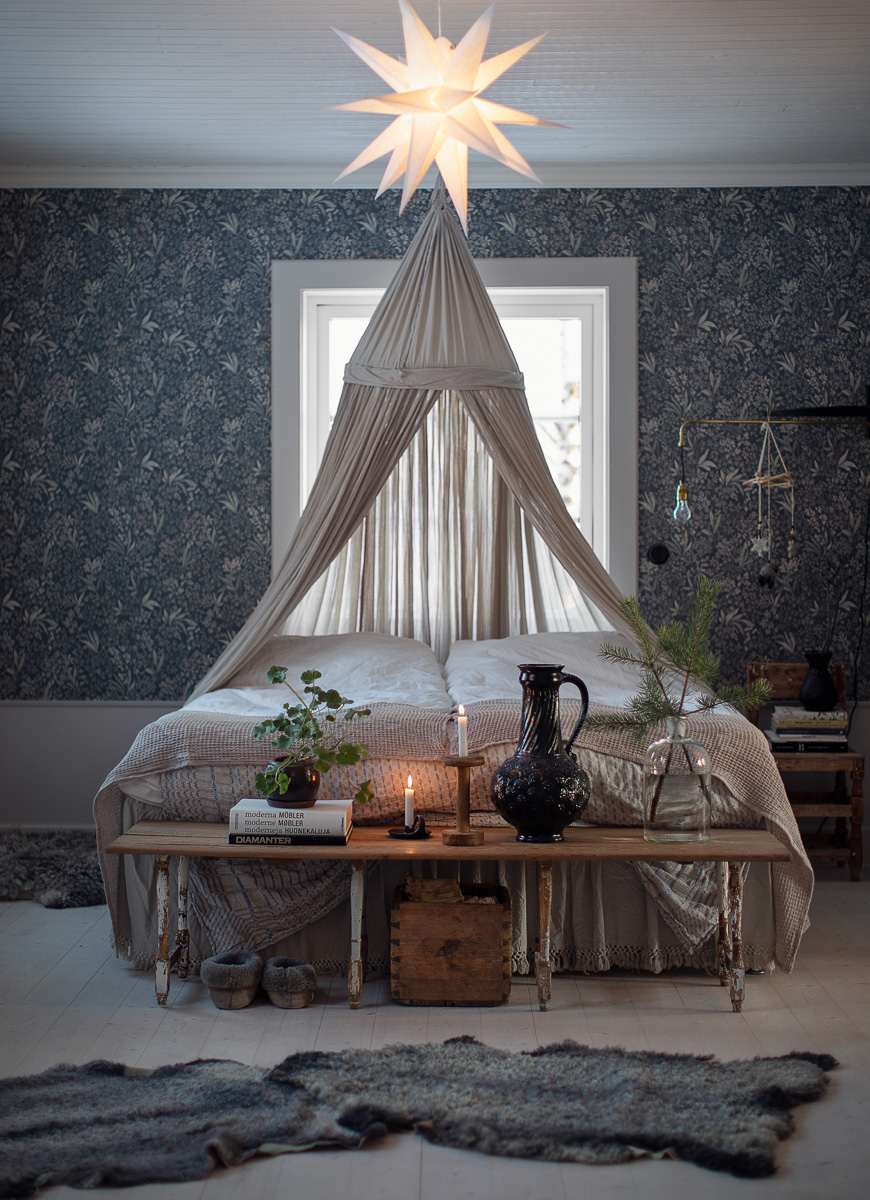 Säng med sänghimmel bakom, tända ljus , blommig tapet