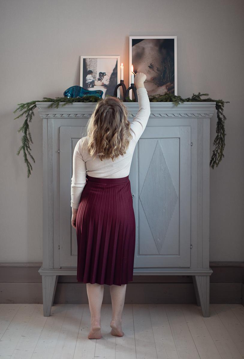 Kvinna tänder ljus på en stor byrå