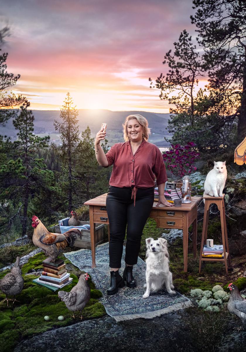 Lalinda står intill ett skrivbord på ett berg i Höga Kusten, tillsammans med hennes djur